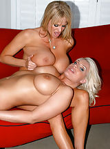 Busty Babes, Kelly Madison and Sadie Swede sit on a cock on a red sofa.