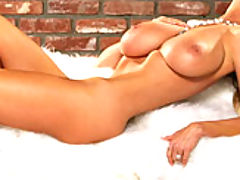 Kelly strips off her white furry vest and lays down on white fur to bounce her tits around.