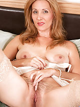 Busty Sluts, Sex starved cougar Camilla shoves a big suction cup dildo deep inside of her hairy juice box